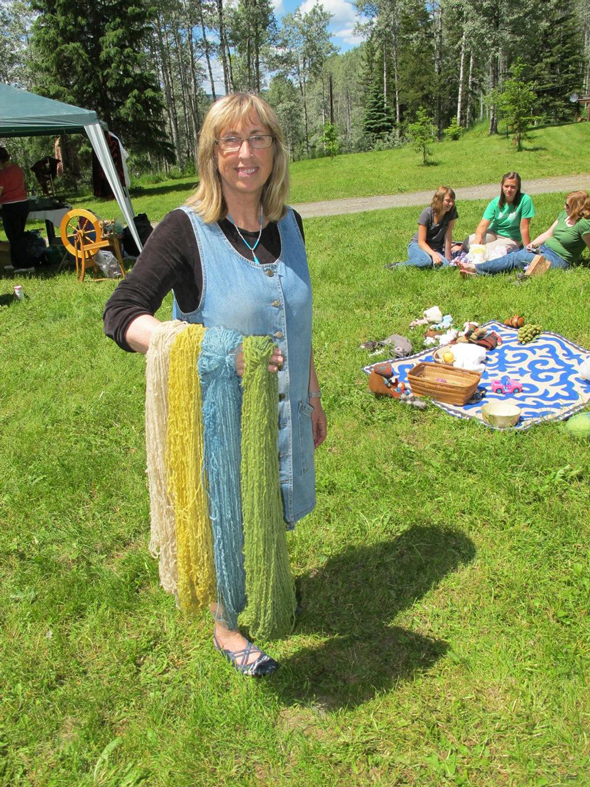 Maureen LeBourdais with handspun wool skeins fresh from the dyepot. From top to bottom: yellow from golden marguerites, blue from indigo, and green from the yellow skein dyed with indigo. Photo: Liliana Dragowska