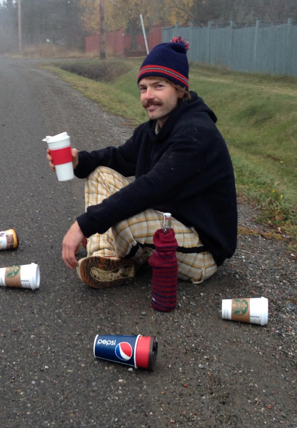 Sitting beside a collection of waste from the now-clean roadside behind him, Oliver wields his refillable mug and bottle and is happy to not to be part of the problem. Photo: Gilly Tew