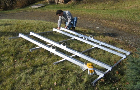 Joe Lade of earthRight builds a solar panel pole mount on the ground prior to hoisting it to a pole and attaching the panels. Photo: Ron Young