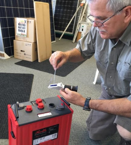 Ron Young uses a refractometer to test specific gravity in a battery.  Photo credit: earthRight Solar