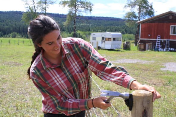 Zetteh Gunner places the electric fence insulator on the page wire fence. Photo: Angela Abrahão