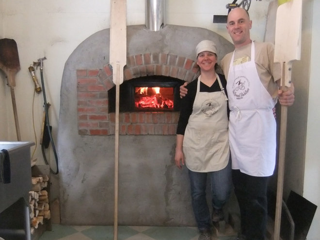 Owners, Kate Sulis and Tim Hathaway at the Bread Peddler in front of their handbuilt wood-fired oven. Enjoy!