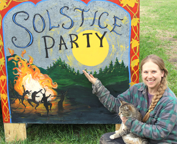 Terri Smith sitting in front of last year's Solstice celebration sign. Photo: Mark Rupp